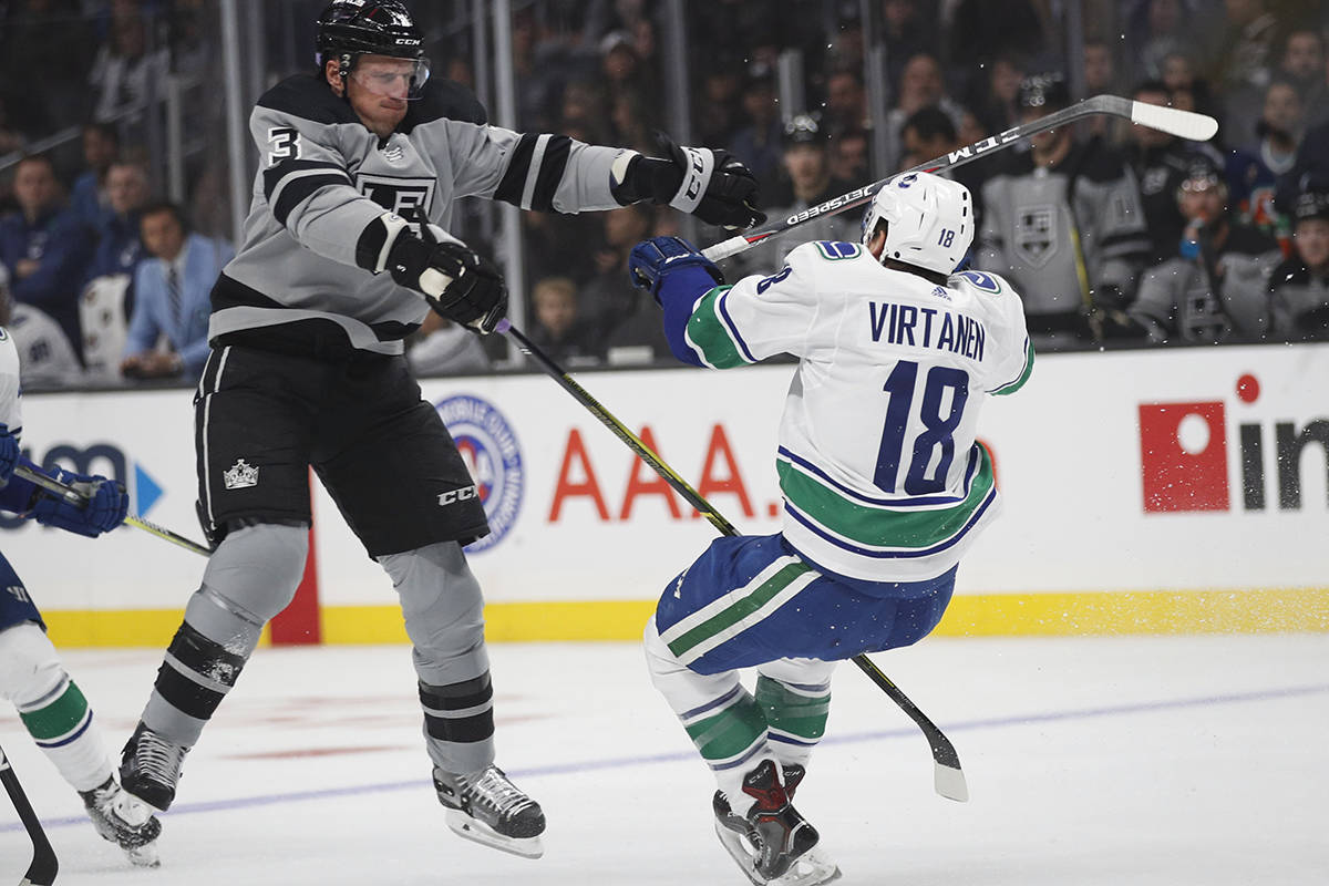 Vancouver Canucks' Jake Virtanen, right, is checked by Los Angeles Kings' Dion Phaneuf during the first period of an NHL hockey game Saturday, Nov. 24, 2018, in Los Angeles. (AP Photo/Jae C. Hong)