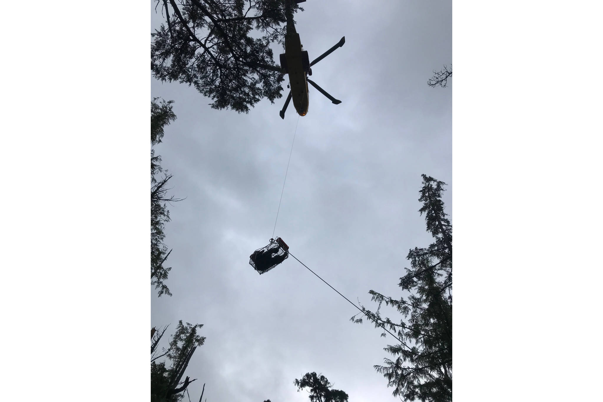 Photo of patient being hoisted up to CH-149 Cormorant. Photo by 442 Transport and Rescue Squadron.